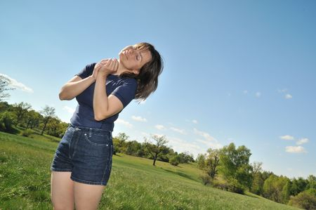 enyoing: Woman enyoing life outdoors in green sunny park (pleasure expression) with blue sky background Stock Photo