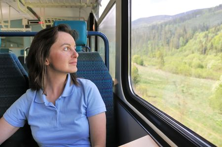 Young woman passanger sitting inside train and looking trough window photo