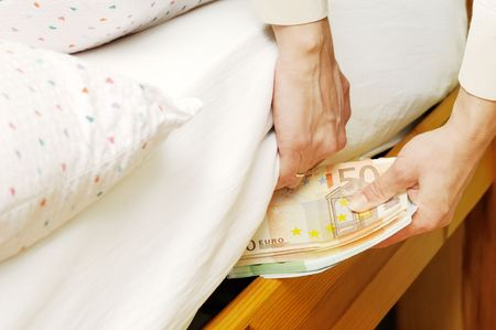 bedclothes: Hands with money hide them under mattress