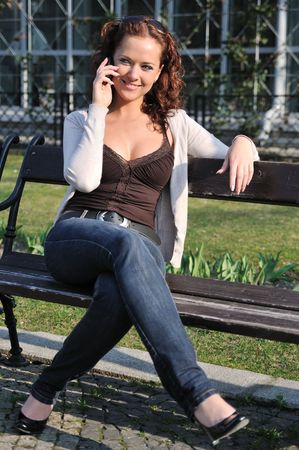Young smiling woman sitting on berm calling with mobile phone with building in background photo