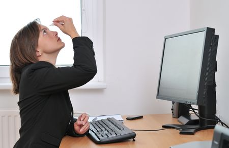 Detail of young business person (woman) applying eye drops on workplace - computer on table Stock Photo - 5237281