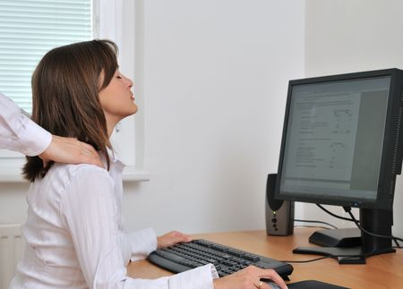 Business person (woman) on workplace with computer receiving neck massage from colleague (only hands visible) photo