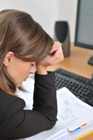 epuise: Young fatigu� et d�prim� affaires personne (femme), assis � table avec un ordinateur et des documents Banque d'images