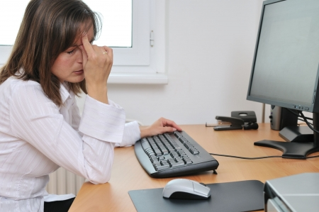 headache: Young tired business woman with headache sitting at computer in workplace holding head