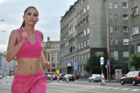 Young woman running and training in city streets - cars and building (traffic background)
