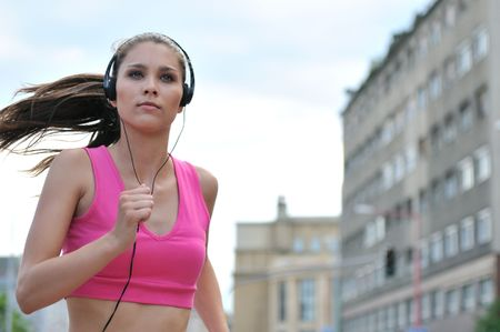 Person (young beautiful woman) listening music running (jogging) in city street photo