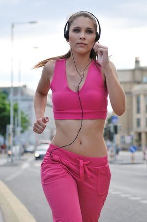 young woman running: Person (young beautiful woman) listening music running (jogging) in city street