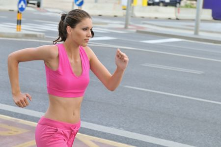 Person (young beautiful woman) running and training in city road