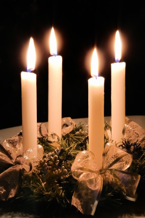 Christmas advent wreath with burning candles laid on table with black background photo
