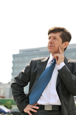 Portrait of thinking senior business man looking away with building in background photo
