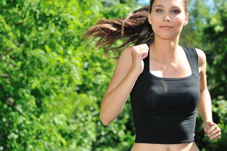 hacer footing: Joven mujer hermosa en la gesti�n de color de rosa (jogging) al aire libre en el parque en el d�a de sol