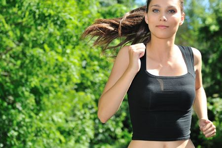 Young beautiful woman in pink running (jogging) outdoor in park on sunny day