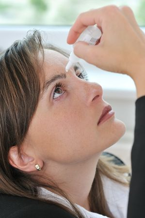 Eyes health care - detail of young woman applying eye drops  Stock Photo
