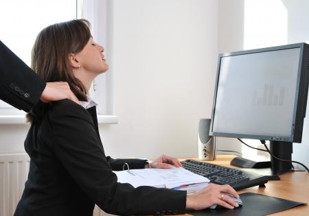 massaggio collo: Business persona (donna) sul posto di lavoro con i computer che si riceve il massaggio del collo dal collega (mani visibile solo)