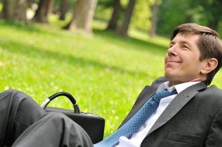 Senior people series - detail of cheerful mature business man siting on grass and relaxing in park photo