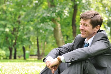 Senior people series - smiling mature business man siting on green grass and relaxing in park photo