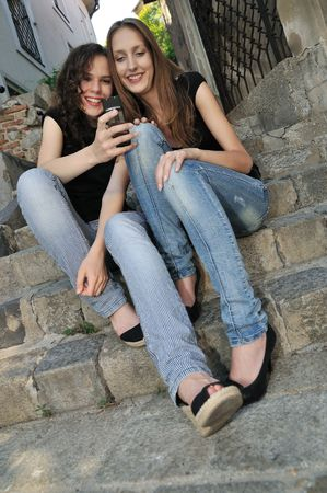 Youth lifestyle - two smiling friends (girls) siting on stairs outdoors with mobile phone Stock Photo - 5429551