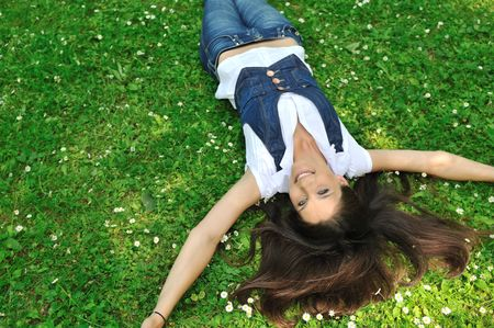 head down: Teenage girl lying in fresh green grass with flowers - above view
