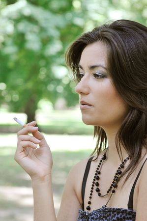 Portrait of young woman smoking cigarette outdoors in sunny green park photo