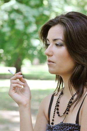 joven fumando: Retrato de joven mujer de cigarrillos fumar al aire libre en el parque verde de sol