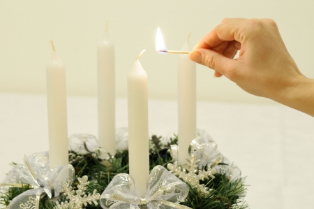 advent: Christmas advent wreath on table - hand is going to light first candle                       Stock Photo