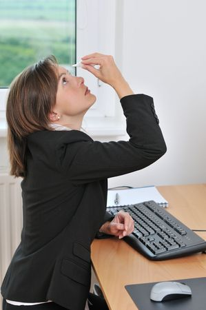 Detail of young business woman applying eye drops on workplace window in background photo