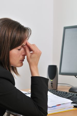 tired eyes: Young business person (woman) has headache and tired eyes are closed - computer and papers on work table Stock Photo