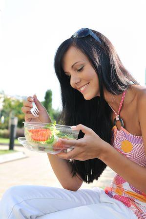 pause repas: Jeune femme belle ayant la pause d�jeuner et mang� de la salade dans un r�cipient en plastique � l'ext�rieur Banque d'images