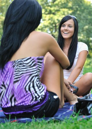 Youth lifestyle series - two young friends talking outdoors in park. Stock Photo - 5509458