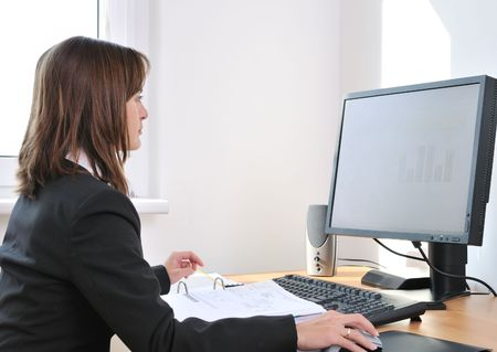 routines: Business person (young woman) works at table with computer - office interior