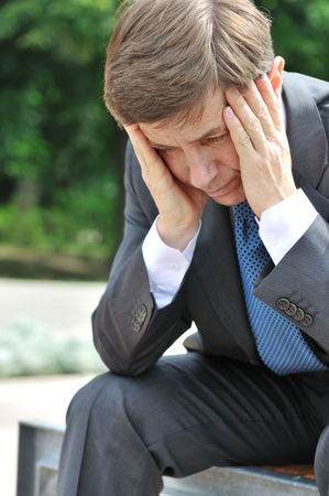 Portrait of depressed senior business man with head in hands siting on bench outdoors photo