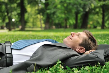 Senior people series - mature business man lying on grass and relaxing in park