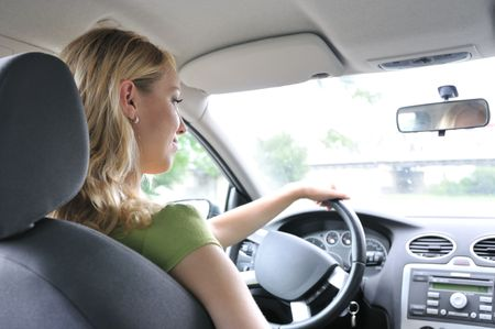 Lifestyle shot of young cheerful woman driving car - rear view photo