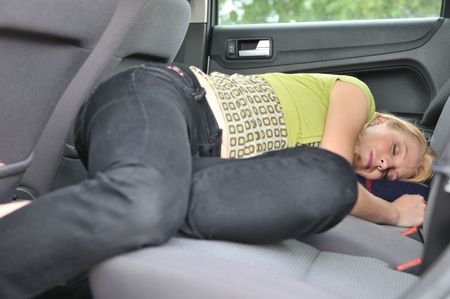 Young beautiful blond woman sleeps in car on back seat - lifestyle portrait photo