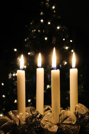 four month: Christmas advent wreath with burning candles. Lights on x-mas tree in background