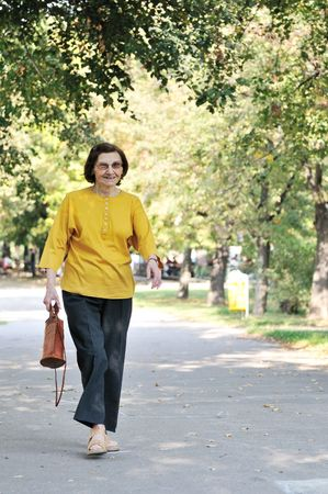Energic and smiling 80 something senior woman wlaking in park on sunny day                      photo