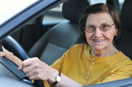 Active senior woman - smiling retired lady driving car, detail