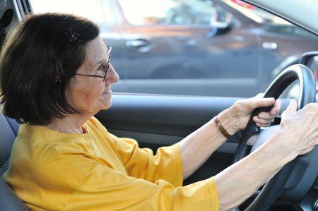 Active senior woman - grandmother driving car, detail photo