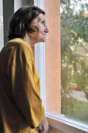 Solitude concept  - sad 80s senior woman looking through window at home                     photo