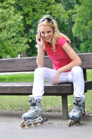 Young smiling woman wearing rollerblades calling with mobilephone outdoors photo