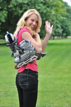 Young smiling woman with rollerskates giving good bye gesture with hand. Outdoors in park.