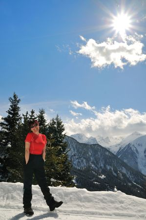 Portrait of senior woman in mountain snow winter land with blue sky, sun and clouds photo