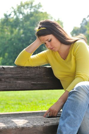 Portrait of worried teenager siting on bench in park photo