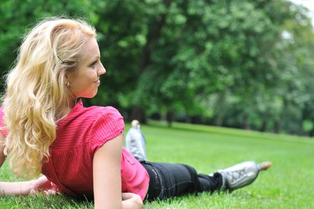Young smiling woman relaxing in green grass after roller skating - rear view photo