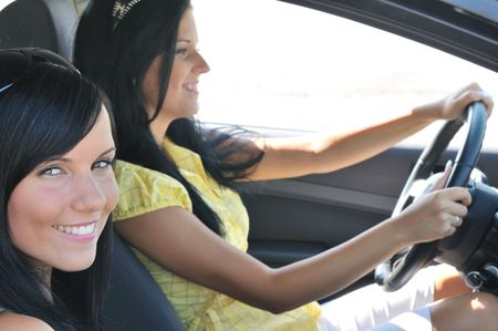 Youth lifestyle - two smiling friends (women) driving in car photo