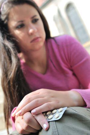 decide: Tomar o no - mujer joven (adolescente) decide mientras mantiene las p�ldoras, se centran en las manos
