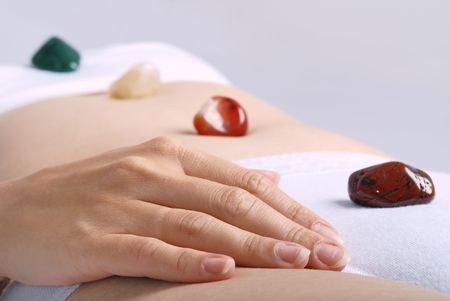 Alternative medicine - healing by semiprecious gems placed on body chakras, shallow depth of field photo