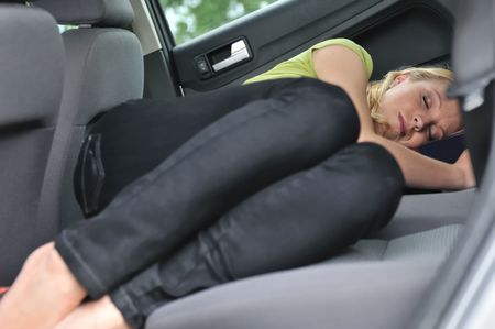 girl sleep: Young beautiful blond woman sleeps in car on back seat - lifestyle portrait Stock Photo