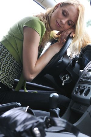 Young beautiful blond woman sleeps in car on steering wheel - detail portrait photo
