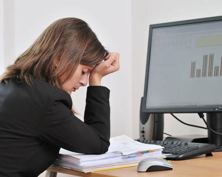 Tired young business woman in depression sitting at computer on workplace Stock Photo